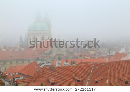 Thick layer of fog above Prague old town buildings and St Nicholas Church, Czech Republic - stock photo
