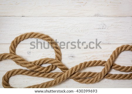 thick marine rope on white boards, copyspace - stock photo