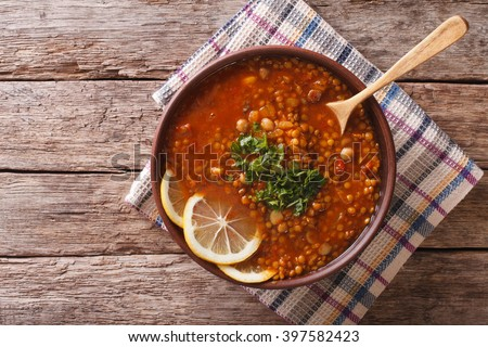 Thick Moroccan Harira soup in a bowl close-up on the table. Horizontal view from above