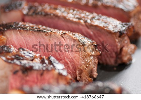 thick ribeye steak seared rare on a cast iron grill - stock photo