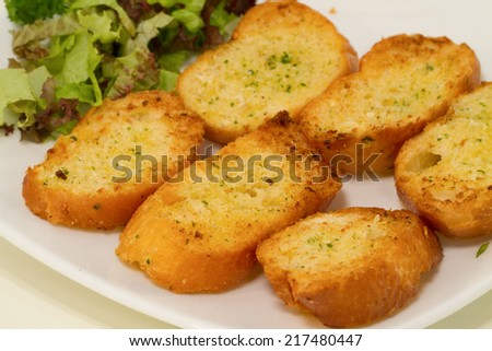 Thick slices of freshly baked garlic bread seasoned with butter and herbs. Macro with extremely shallow dof. - stock photo