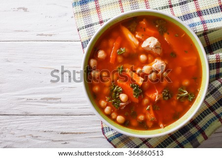 Thick soup chickpeas with chicken and vegetables on the table. Horizontal top view - stock photo