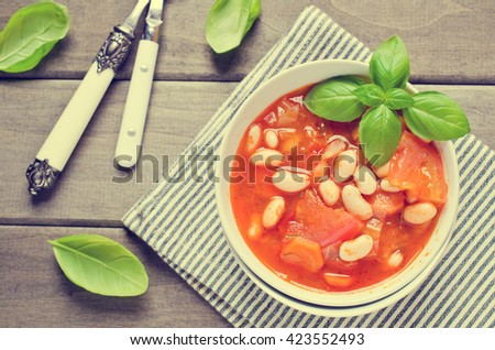 Thick soup with beans and vegetables on a wooden background. Selective focus. - stock photo