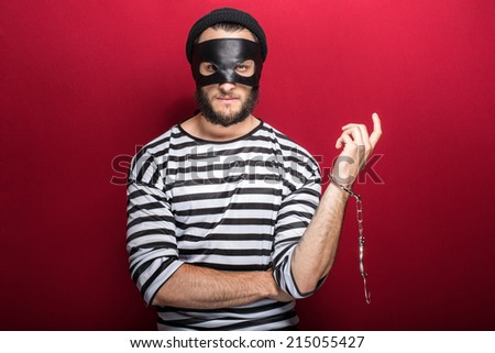 Thief arrested as a consequence of his crime. Portrait on red background  - stock photo