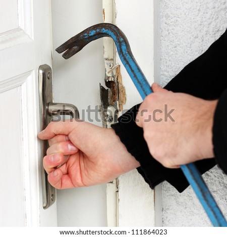 Thief breaking door - stock photo