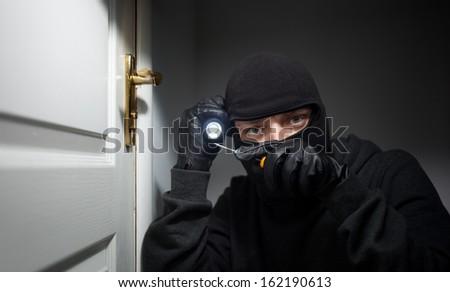 Thief Burglar opening  door - stock photo