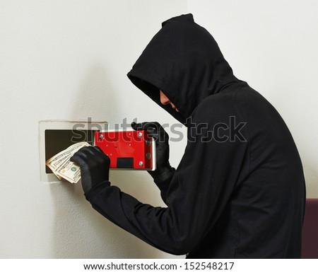Thief burglar stealing euro money during home safe codebreaking - stock photo