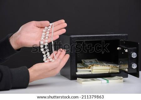 Thief burglar stealing money during home safe codebreaking - stock photo