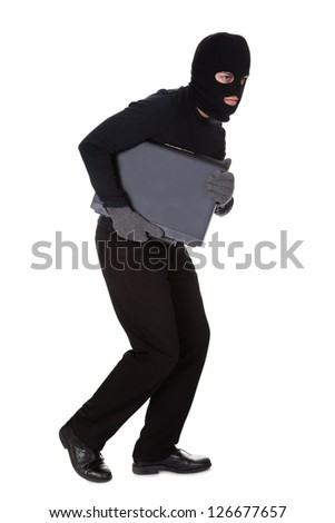 Thief dressed in black and wearing a balaclava stealing a laptop computer and making a furtive escape isolated on white - stock photo
