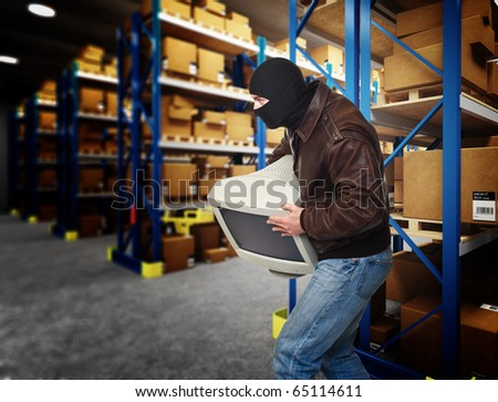 thief hold pc monitor  in  classic warehouse - stock photo