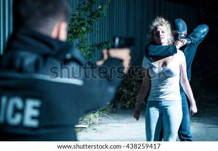 Thief holding a woman hostage while a policeman is pointing gun at him - stock photo