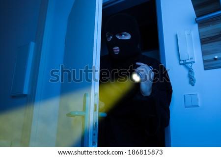Thief holding flashlight while secretly entering into house - stock photo