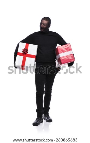 Thief in action carrying presents with balaclava on his face, dressed in black. Studio shot on white background. - stock photo