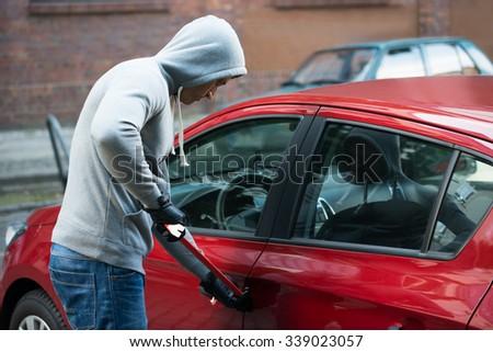 Thief In Hooded Jacket Using Crowbar To Open Car's Door - stock photo