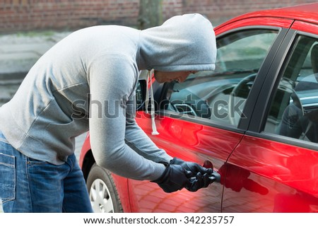 Thief In Hooded Jacket Using Tool And Trying To Steal Car - stock photo