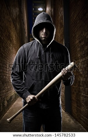 Thief in the hood on a dark alley - stock photo