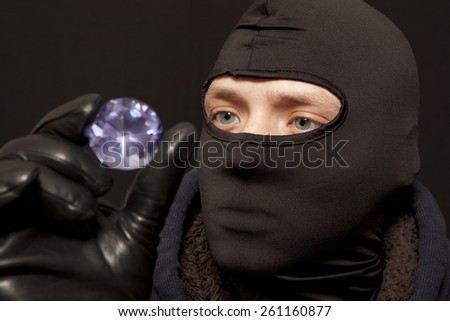 Thief. Man in black mask with a big diamond.Focus on thief - stock photo