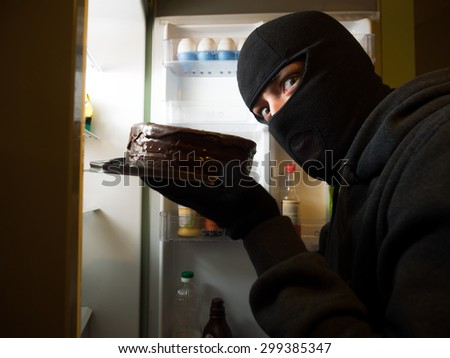 Thief. Man in black mask with a cake. - stock photo