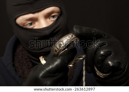 Thief. Man in black mask with a silver bracelet. Focus on bracelet - stock photo