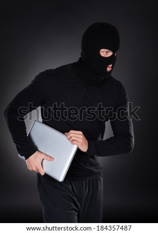 Thief stealing a laptop computer creeping furtively through the darkness as he makes his getaway  conceptual of data and identity theft - stock photo