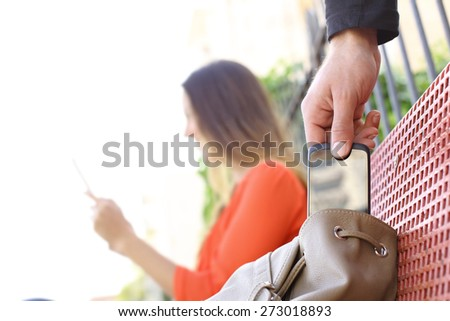 Thief stealing a mobile phone to a woman sitting on a bench in a park - stock photo