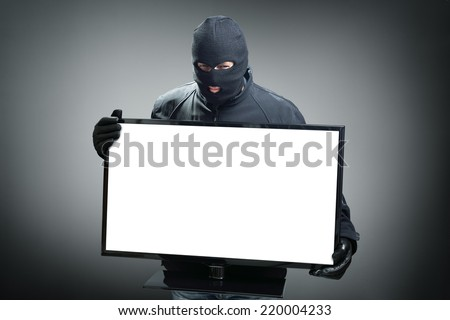 Thief stealing computer monitor or television concept for hacker, security or insurance with space on screen for message - stock photo