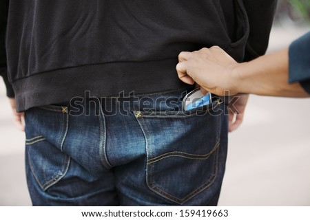 Thief stealing mobile phone from back pocket of a man walking on the street. Pickpocketing smart phone from back pocket of man. - stock photo