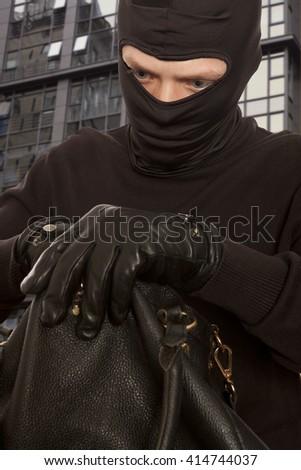 Thief stealing money from women handbag - stock photo