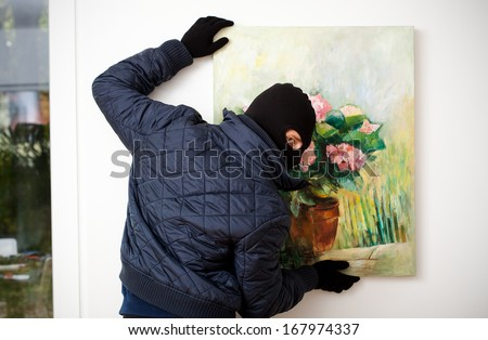 Thief stealing the piece of art from gallery of art. - stock photo