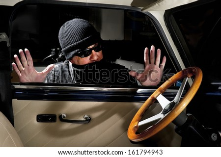 Thief trying to steal a car - stock photo