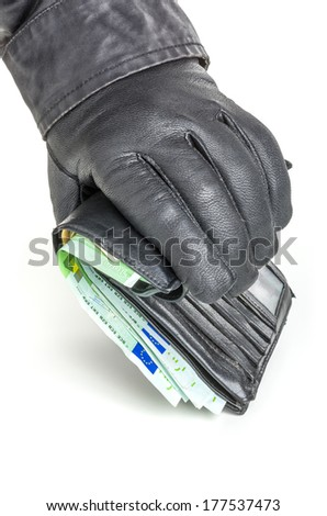 Thief with leather glove is reaching for a wallet - stock photo