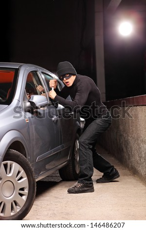 Thief with robbery mask trying to steal a car on a parking lot - stock photo