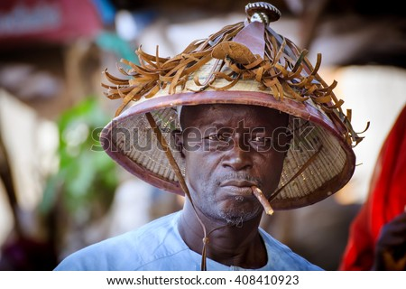 THIES/SENEGAL - NOVEMBER 12, 2013: Portrait of unidentified senegalese man with a wooden stick in his mouth and a big traditional hat - stock photo