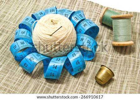 thimble, yarn and spools of thread on fabric - stock photo