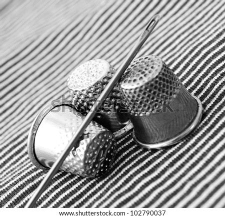 Thimbles and needle on a fabric. - stock photo