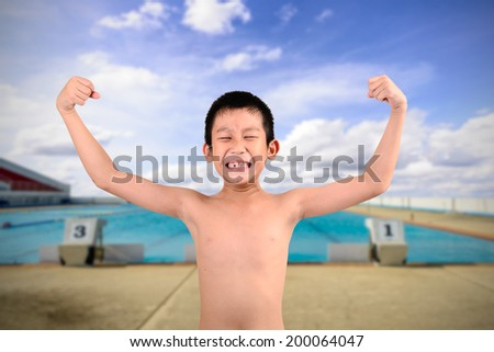 Thin boy showing his muscles with background swimming pool platform. - stock photo