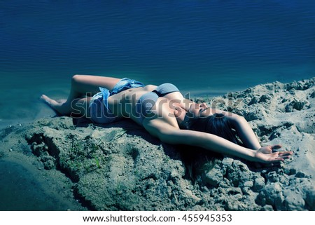 thin fashion model is like a mermaid in the sand on the shore of the island under water - stock photo