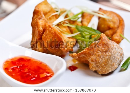 Thin flour sheet stuffed with seasoned chicken and deep fried, served with spicy plum sauce  - stock photo