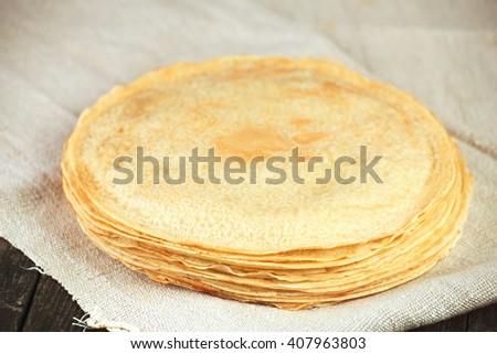 Thin golden crepes pancakes on linen towel. Tasty breakfast. - stock photo