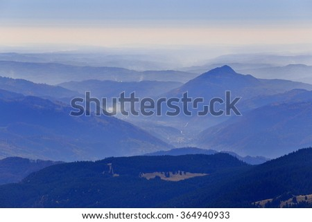 Thin layer of fog cover distant valley and summits, Romania - stock photo