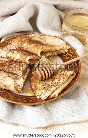 Thin pancakes, crepes with  syrup on wooden cutting board. Pancake week, mardi gras, maslenitsa holidays - stock photo