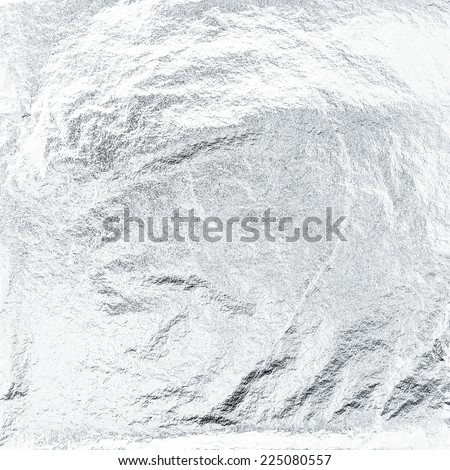 Thin sheet of silver leaf background with shiny uneven surface  - stock photo