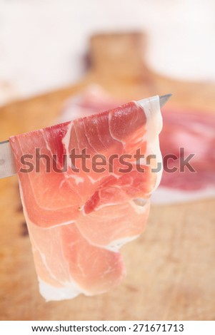 Thin slice of Prosciutto on a knife - stock photo