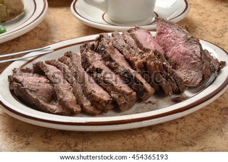 Thin sliced medium rare beef sirloin roast on a serving platter - stock photo