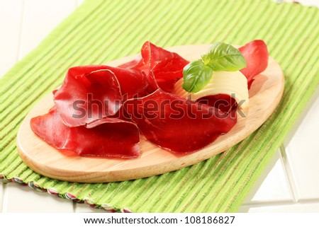 Thin slices of dried meat on a cutting board - stock photo