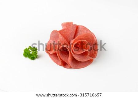 thin slices of salami on white background - stock photo