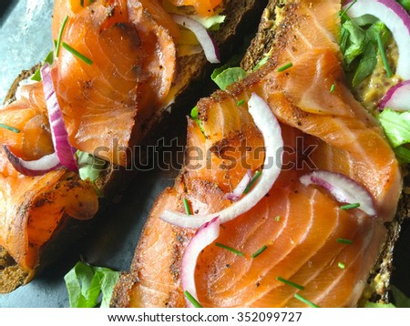 Thin slices of salmon on dark bread with onion and chives - stock photo