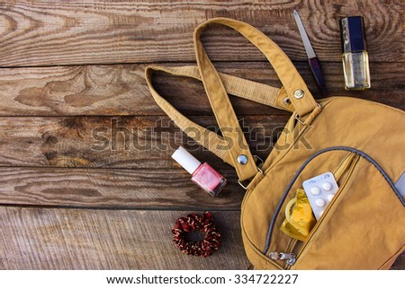 Things from open lady handbag. Cosmetics, female accessories, birth control pill and condom falls out of pocket with handbags on wooden background. Toned image.  - stock photo