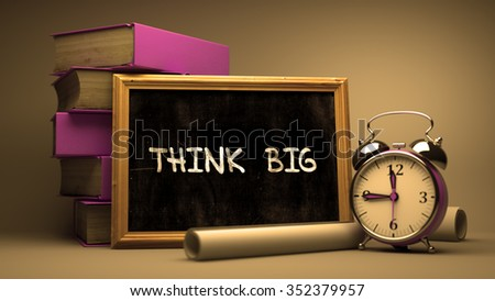 Think Big. Inspirational Quote on a Blackboard. Composition with Small Chalkboard and Stack of Books, Alarm Clock and Rolls of Paper on Blurred Background. Toned Image. - stock photo