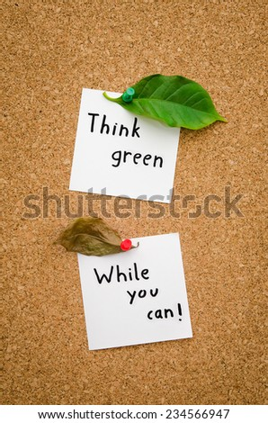 Think green while you can suggesting the ecologist green environmental movement and an important message for ecology everywhere with a dried up leaf and a green one - stock photo